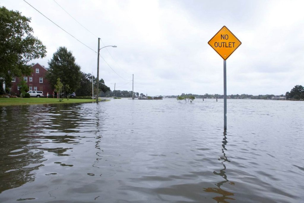 A street sign rises above flood waters as high tide fills the street behind it in Norfolk, Va., last year. Flooding in the area is becoming more frequent. (Timothy C. Wright for The Washington Post.)